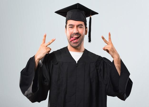 Hombre en su día de graduación universidad mostrando lengua en la cámara con aspecto divertido