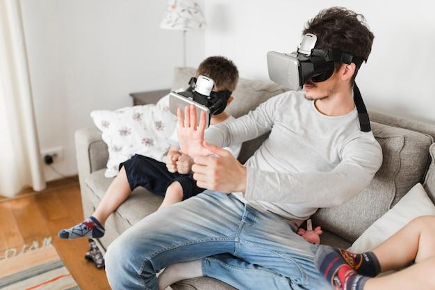 El hombre y su hijo sentado en el sofá con gafas de realidad virtual