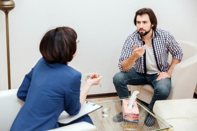 El hombre y su médico tienen una conversación. es muy emotivo. chico barbudo está agitando su mano. el terapeuta está haciendo lo mismo. están sentados en la sala blanca.