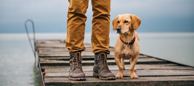 El hombre y su perro de pie en el muelle