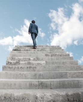 Hombre subiendo por escaleras al cielo