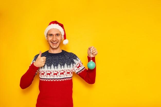 Hombre de suéter de navidad con renos da thumbs up aislado fondo amarillo con espacio para tex