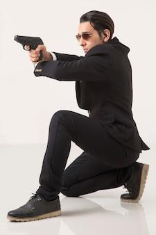 Hombre en suite de negocios y pistola sobre fondo blanco, sentado y apuntando
