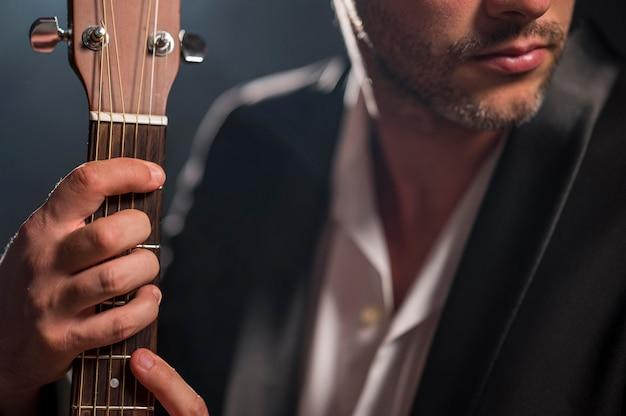 Hombre sujetando un acorde en primer plano de la guitarra