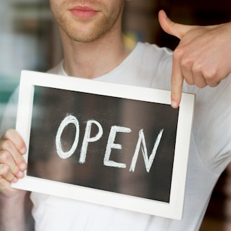 Hombre sujetando y apuntando al cartel de cafetería abierta
