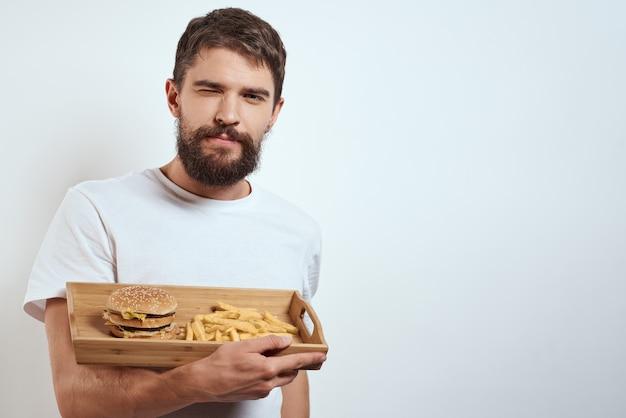 Hombre sujetando una bandeja con comida chatarra aislada