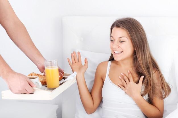 Hombre sujetando la bandeja del desayuno a la mujer en la cama