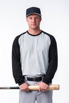 Hombre sujetando un bate de béisbol y posando