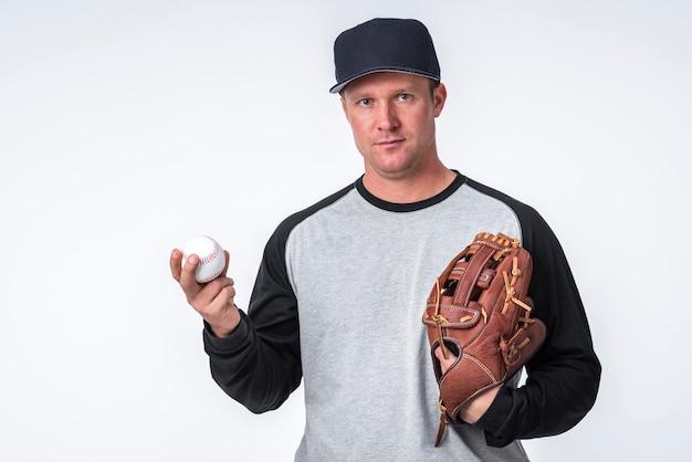 Hombre sujetando béisbol y guante