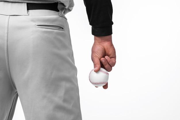Hombre sujetando el béisbol con vista posterior