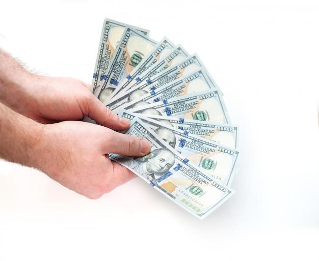 Hombre sujetando billetes de cien dólares desplegados en un blanco