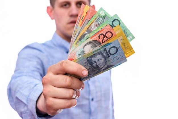 Hombre sujetando billetes de dólar australiano aislado en blanco