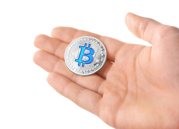 Hombre sujetando bitcoin plateado sobre blanco
