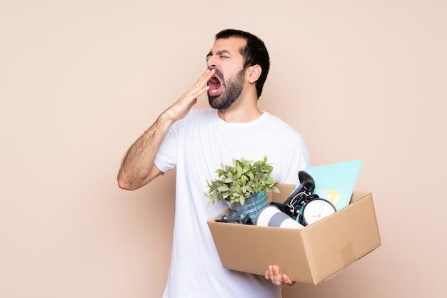 Hombre sujetando una caja y moviéndose en un nuevo hogar sobre bostezos aislados y cubriendo la boca abierta con la mano