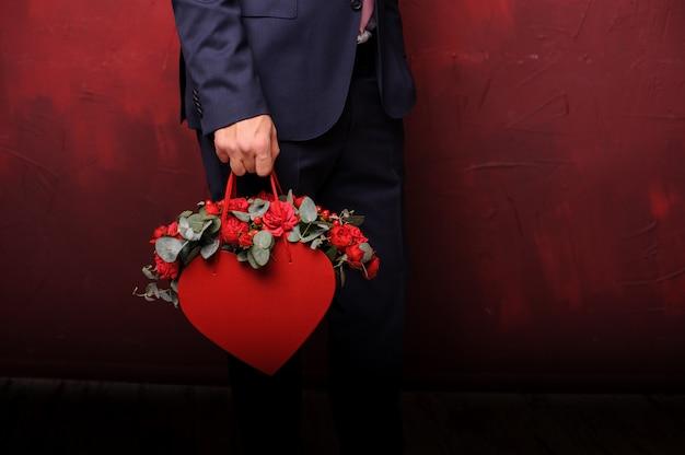 Hombre sujetando una caja roja de flores