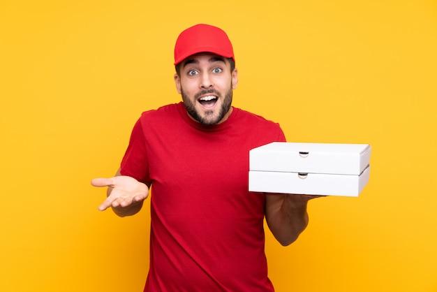Hombre sujetando cajas de pizzas sobre pared aislada
