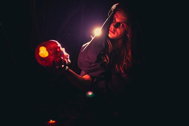 Hombre sujetando una calavera en la oscuridad y mirando a cámara
