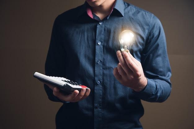 Hombre sujetando calculadora y lámpara sobre superficie marrón