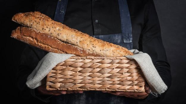 Hombre sujetando una canasta con pan