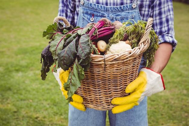 Hombre sujetando una canasta de verduras recién cosechadas en el jardín