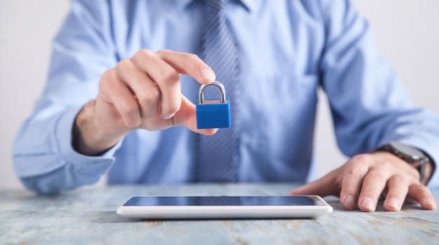 Hombre sujetando candado tableta en el escritorio. seguridad de internet