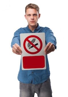 Hombre sujetando un cartel de prohibido fumar