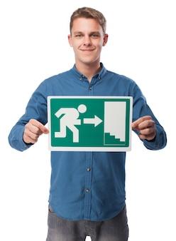 Hombre sujetando un cartel de salida de emergencia