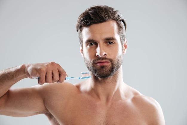 Hombre sujetando el cepillo de dientes en manos aisladas