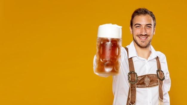 Hombre sujetando cerveza pinta con espacio de copia