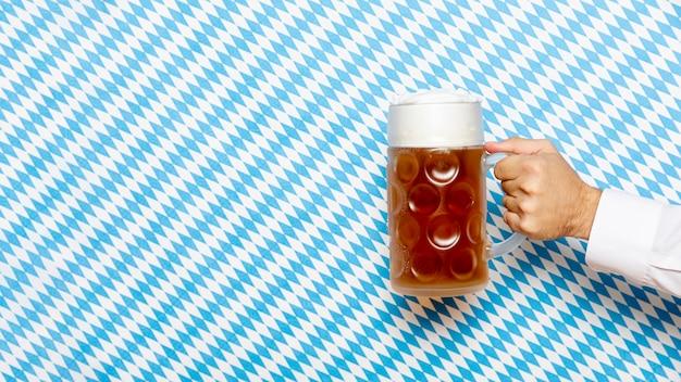 Hombre sujetando cerveza pinta con fondo estampado