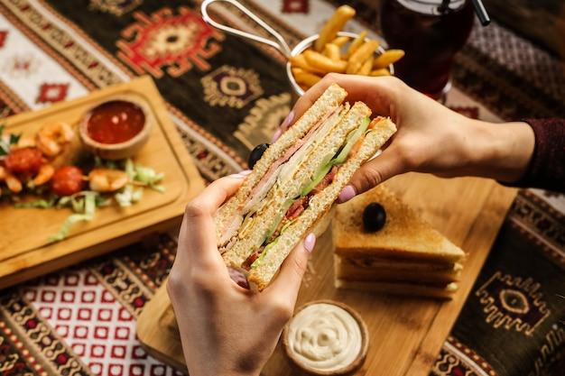 Hombre sujetando club sandwich