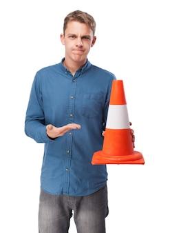 Hombre sujetando un cono de tráfico