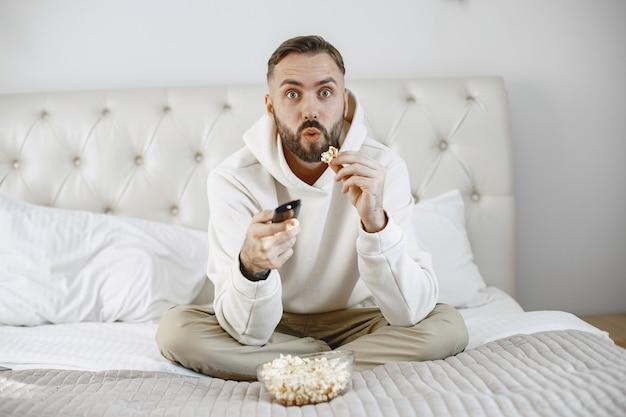 Hombre sujetando el control remoto con tazón de palomitas de maíz