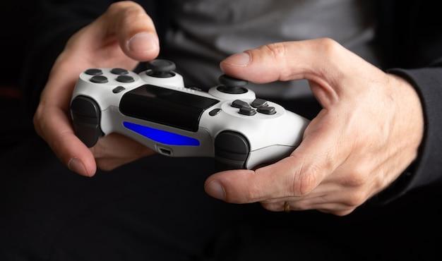 Hombre sujetando el controlador de juego blanco - seletive focus