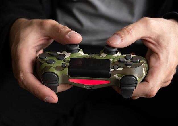 Hombre sujetando el controlador de juego de camuflaje - seletive focus