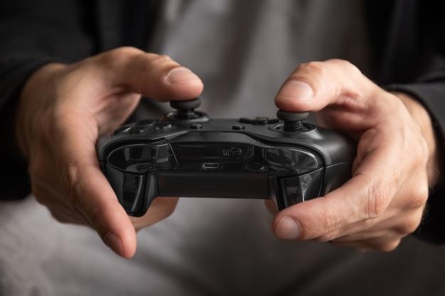 Hombre sujetando el controlador de juego negro - enfoque selectivo