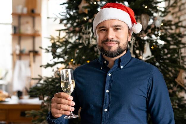 Hombre sujetando una copa de champán en navidad