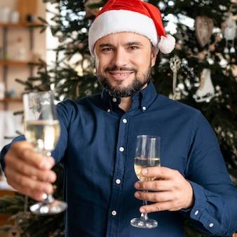 Hombre sujetando copas de champán en navidad