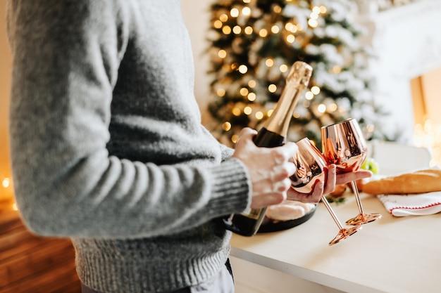 Hombre sujetando copas y champaña