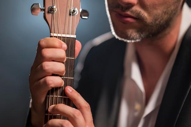 Hombre sujetando las cuerdas de una guitarra