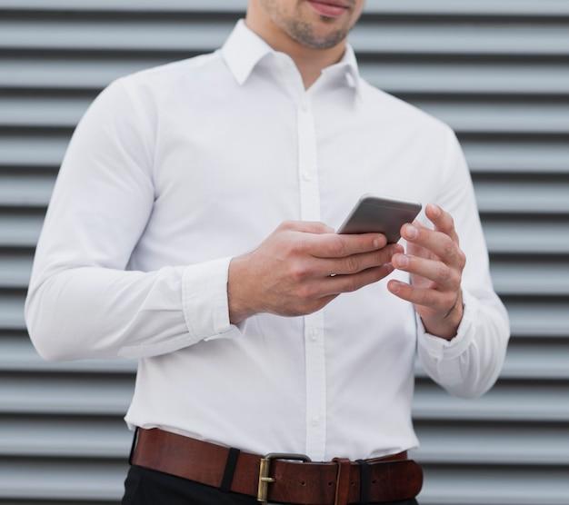 Hombre sujetando el dispositivo móvil de cerca