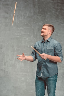 Hombre sujetando dos baquetas sobre espacio gris