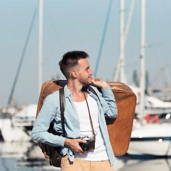 Hombre sujetando el equipaje de tiro medio
