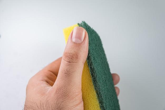 Hombre sujetando una esponja de cocina sobre el fondo blanco.