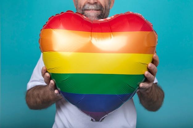 Hombre sujetando un globo de color arcoiris
