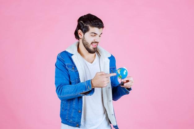 Hombre sujetando un globo terráqueo y tratando de encontrar una ubicación