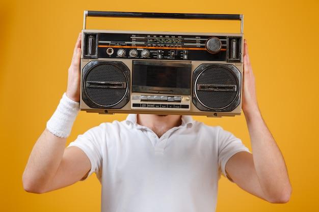 Hombre sujetando la grabadora que cubre la cara