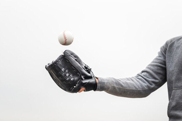Hombre sujetando el guante y lanzando béisbol