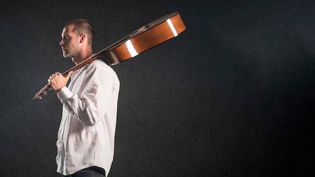 Hombre sujetando la guitarra acústica en estudio