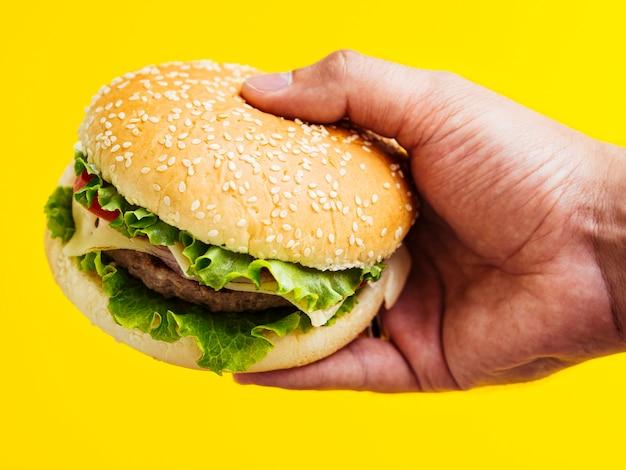 Hombre sujetando una hamburguesa con queso con semillas